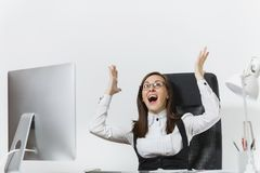 Belle femme d'affaires dans le fonctionnement de costume et en verre à l'ordinateur avec des documents dans le bureau léger Image libre de droits