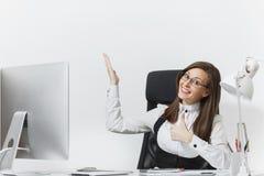 Belle femme d'affaires dans le fonctionnement de costume et en verre à l'ordinateur avec des documents dans le bureau léger Photographie stock