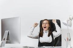 Belle femme d'affaires dans le fonctionnement de costume et en verre à l'ordinateur avec des documents dans le bureau léger Photos stock