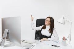 Belle femme d'affaires dans le fonctionnement de costume et en verre à l'ordinateur avec des documents dans le bureau léger Images stock