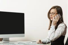 Belle femme d'affaires dans le fonctionnement de costume et en verre à l'ordinateur avec des documents dans le bureau léger Photo stock