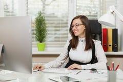Belle femme d'affaires dans le fonctionnement de costume et en verre à l'ordinateur avec des documents dans le bureau léger photo libre de droits