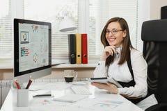 Belle femme d'affaires dans le fonctionnement de costume et en verre à l'ordinateur avec des documents dans le bureau léger image stock