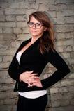Belle femme d'affaires dans un costume noir et verres sur un concept de fond de mur de briques d'un chef féminin fort et réussi Photographie stock