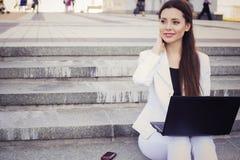 Belle femme d'affaires de brune dans le costume blanc avec le carnet sur son recouvrement, dactylographie, fonctionnant dehors Photographie stock libre de droits
