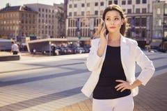 Belle femme d'affaires de brune dans le costume blanc parlant sur un cel Images libres de droits