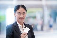 Belle femme d'affaires de sourire avec la carte de visite professionnelle de visite photo stock