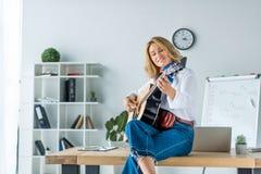 belle femme d'affaires de sourire jouant la guitare acoustique image libre de droits