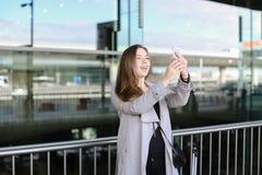 Belle femme d'affaires faisant le selfie par le smartphone près de la mallette et de l'aéroport Photographie stock