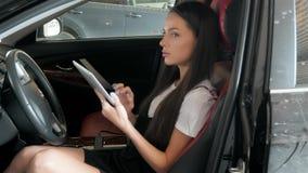 Belle femme d'affaires heureuse à l'aide de la tablette à l'intérieur d'une voiture Photos stock