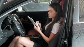 Belle femme d'affaires heureuse à l'aide de la tablette à l'intérieur d'une voiture Photo stock