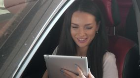 Belle femme d'affaires heureuse à l'aide de la tablette à l'intérieur d'une voiture Images stock