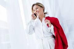 belle femme d'affaires heureuse tenant la veste rouge et parlant par le smartphone photo libre de droits