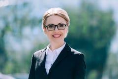 Belle femme d'affaires mûre blonde dans des lunettes souriant à l'appareil-photo Photographie stock