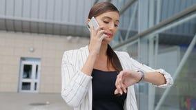 Belle femme d'affaires parlant au téléphone allant travailler clips vidéos