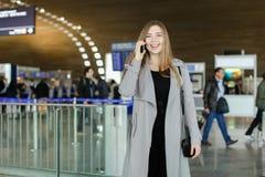 Belle femme d'affaires parlant par le smartphone au hall d'aéroport, au manteau gris de port et au sac Photo libre de droits