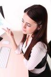 Belle femme d'affaires regardant des papiers elle se tenant en son AR Photographie stock