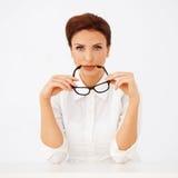 Belle femme d'affaires retenant des lunettes Image stock