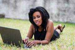 Belle femme d'affaires s'étendant sur l'herbe et à l'aide de l'ordinateur portable image stock