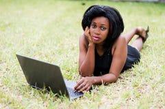 Belle femme d'affaires s'étendant sur l'herbe et à l'aide de l'ordinateur portable images libres de droits