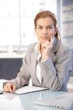 Belle femme d'affaires s'asseyant au bureau Image stock