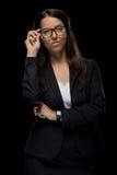 Belle femme d'affaires sûre posant dans les lunettes et le costume noir Photo stock