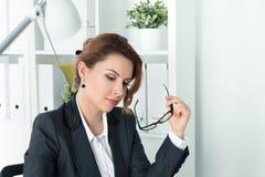 Belle femme d'affaires songeuse s'asseyant à son lieu de travail Photographie stock