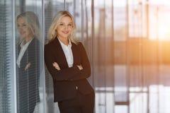 Belle femme d'affaires souriant avec les bras pliés dans le bureau Image stock