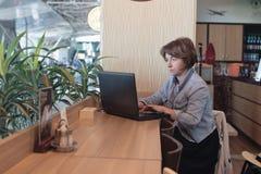 Belle femme d'affaires supérieure s'asseyant au café ayant la conversation téléphonique avec le client E image libre de droits