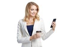 Belle femme d'affaires tenant le verre de papier du café et du téléphone Photo stock