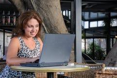 Belle femme d'affaires travaillant avec l'ordinateur portable en café Image stock
