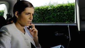 Belle femme d'affaires travaillant avec le PC et le téléphone dans la cabine déçue Images stock