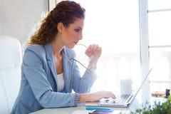 Belle femme d'affaires travaillant avec son ordinateur portable dans le bureau Photographie stock