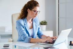 Belle femme d'affaires travaillant avec son ordinateur portable dans le bureau Photos stock