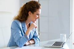 Belle femme d'affaires travaillant avec son ordinateur portable dans le bureau Image libre de droits