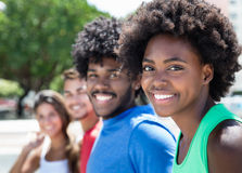 Belle femme d'afro-américain avec quelques amis dans la ville Photographie stock libre de droits