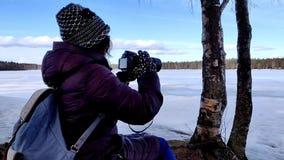 Belle femme d'hiver prenant des photos dans les bois de la nature couverte par neige banque de vidéos