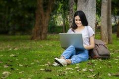 Belle femme d'un étudiant s'asseyant avec l'ordinateur portable et détendant dedans Images libres de droits
