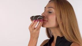 Belle femme d'une chevelure rouge appréciant sentant le beignet délicieux de chocolat banque de vidéos