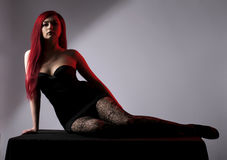 Belle femme d'une chevelure rouge posant au-dessus du gris Image libre de droits