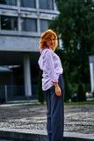 Belle femme d'une cinquantaine d'années avec les cheveux rouges sur une promenade photo stock