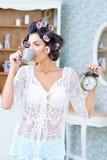 Belle femme dans des bigoudis de cheveux buvant du café pendant le matin Image libre de droits