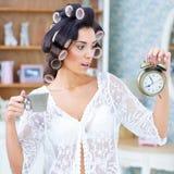 Belle femme dans des bigoudis de cheveux regardant étonnés l'horloge Photos stock
