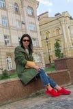 Belle femme dans des espadrilles rouges se reposant sur les étapes Photographie stock