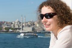 Belle femme dans des lunettes de soleil contre un paysage Images stock