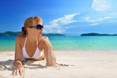 Belle femme dans des lunettes de soleil prenant un bain de soleil sur le beac arénacé blanc Image libre de droits