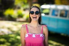 Belle femme dans des lunettes de soleil se tenant en parc Photographie stock libre de droits