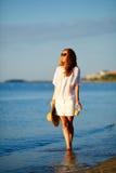 Belle femme dans des vêtements blancs avec le jus d'orange, les lunettes de soleil et le chapeau à disposition sur la plage Photographie stock libre de droits