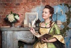 Belle femme dans l'écriture médiévale de robe en journal intime Image stock