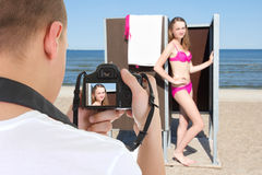 Belle femme dans la carlingue changeante et photographe sur la plage Photo libre de droits